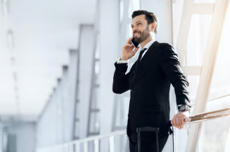 Happy businessman standing in airport, talking on phone